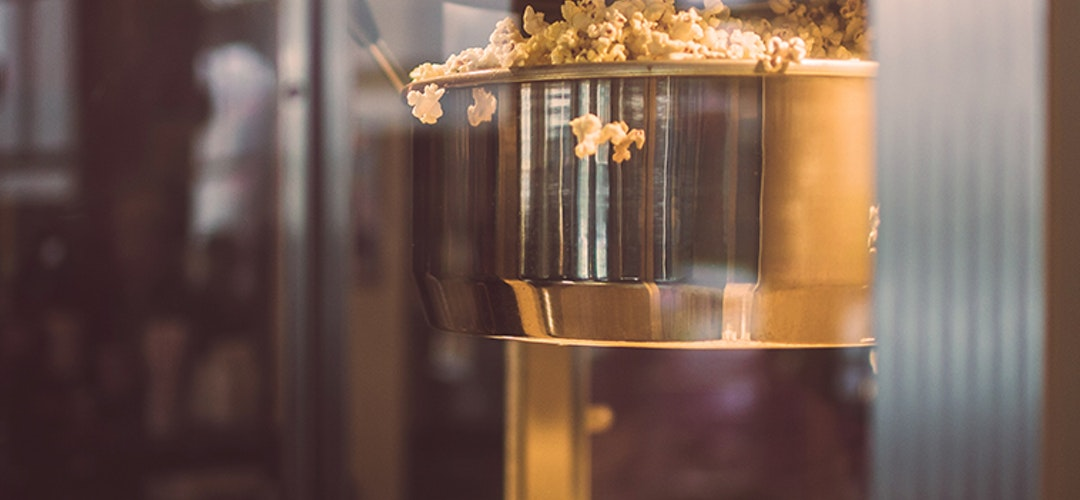 An artistic shot of a class popcorn maker, its metal surface shining almost golden as fresh popcorn cascades out of it.