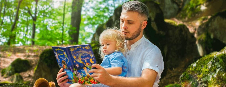 Barn och pappa har högläsning i skogen