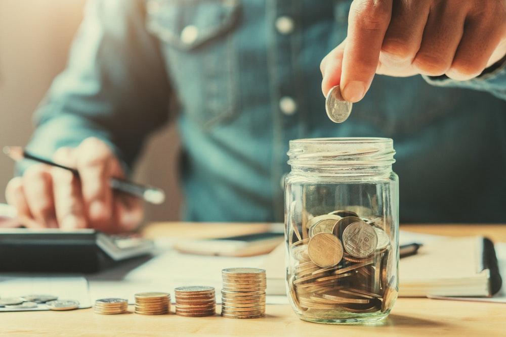 uomo d'affari in possesso di monete mettendo in vetro. concetto di risparmio di denaro per la contabilità finanziaria