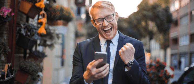Mann schaut auf sein Handy und freut sich