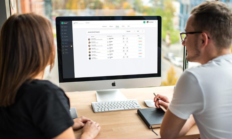 Kollegen schauen auf einen Computer mit einer HR-Software