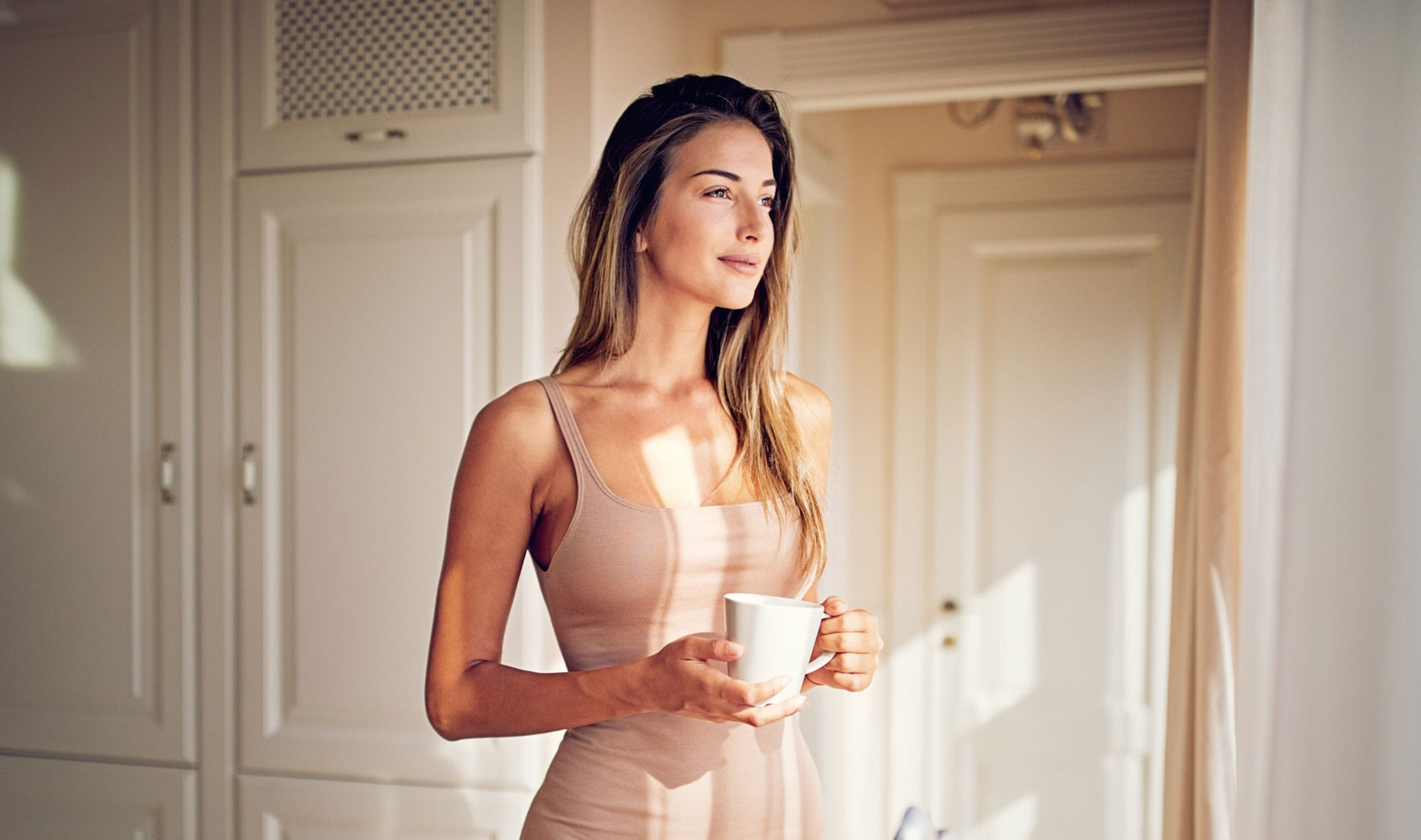 Beautiful Woman Drinking Coffee and Looking Out The Window
