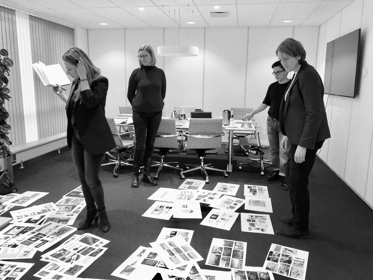 Black and white picture of office with papers on floor and four people working