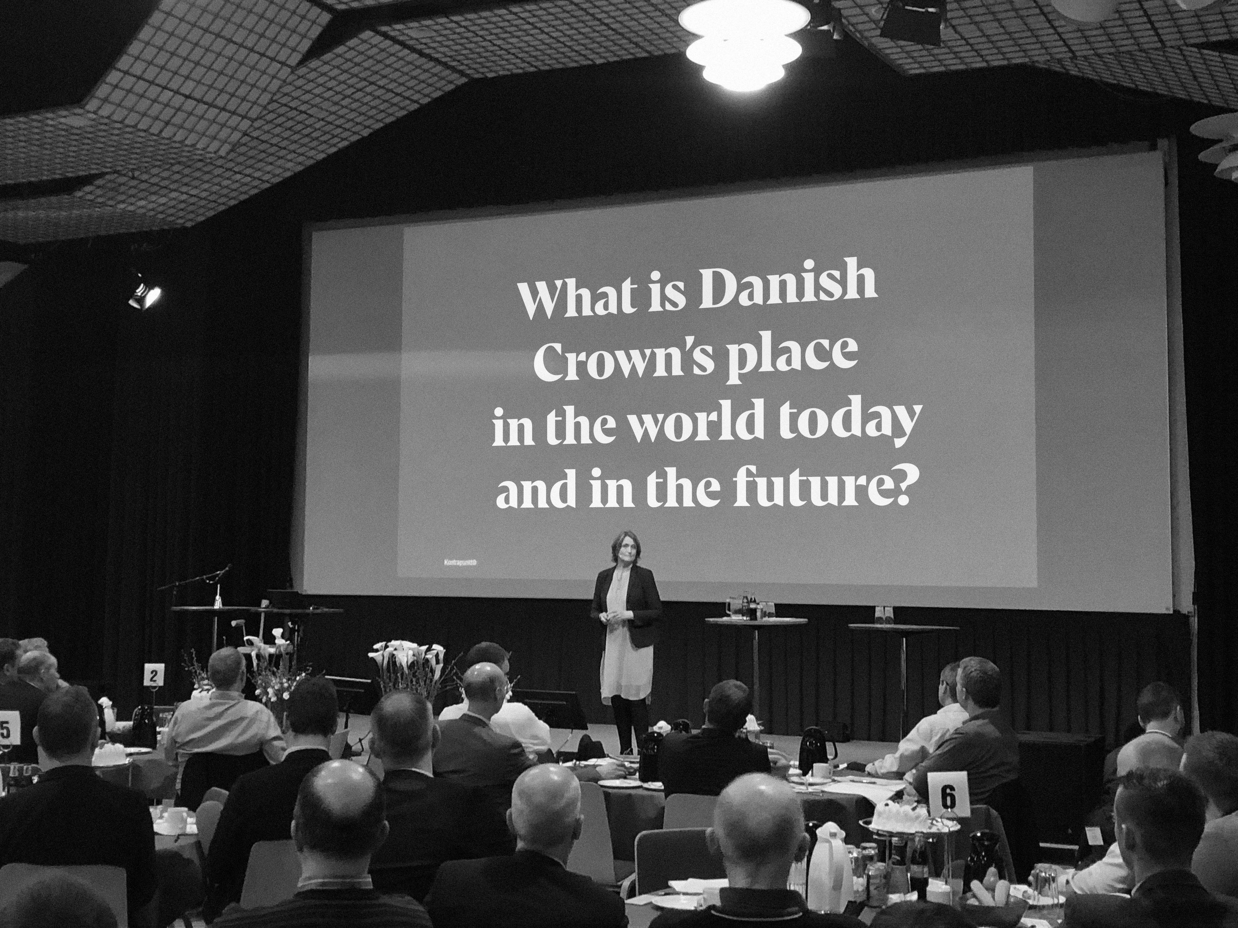 woman standing on stage with backdrop that says What is Danish Crown's place in the world today and the future?