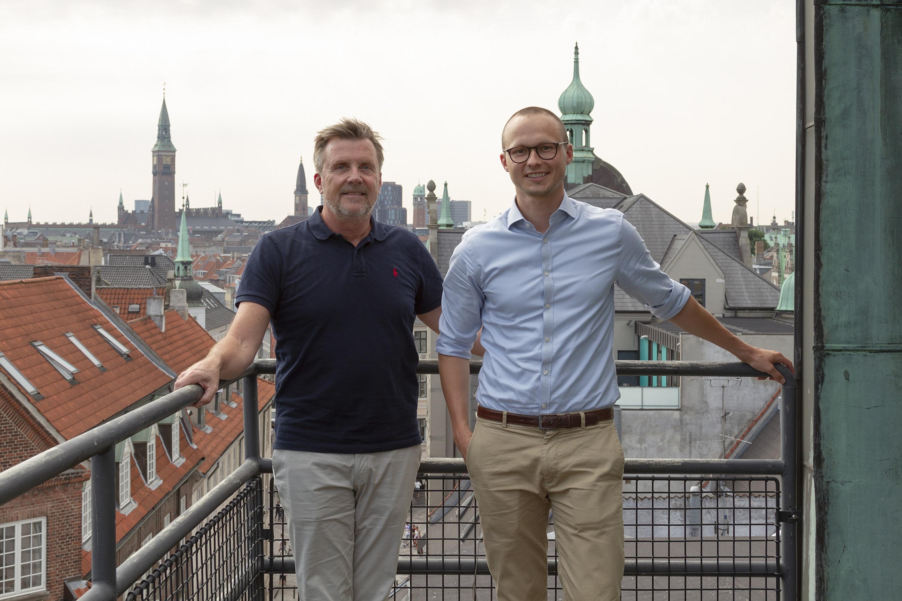 two men looking at camera on copenhagen rooftop