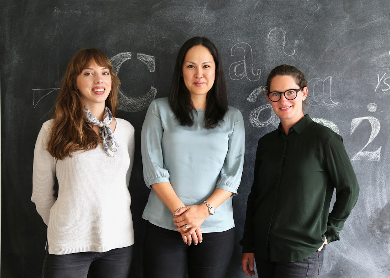 Portrait of three women standing against blackboard