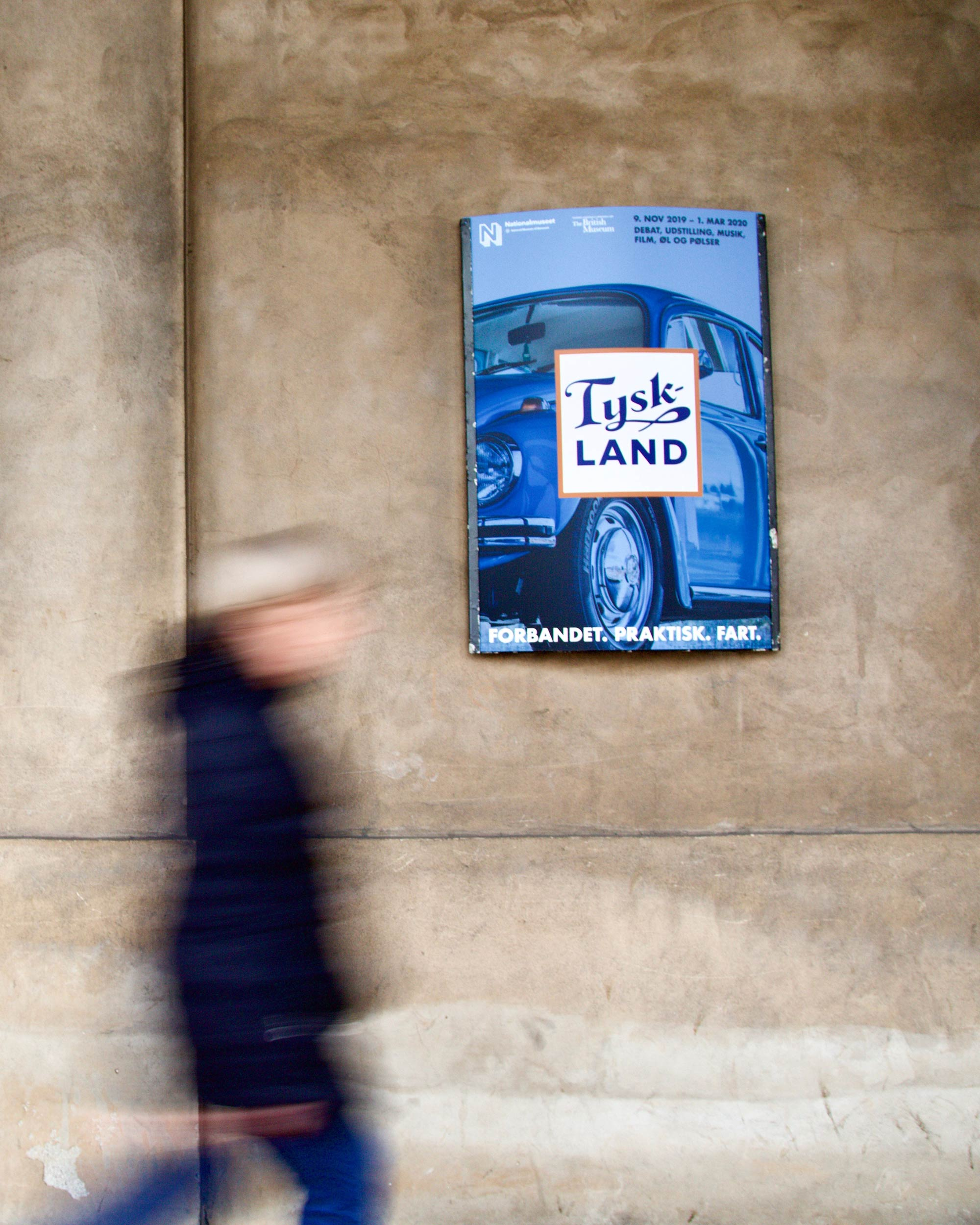 blue poster on wall saying 'Tyskland' with person walking past