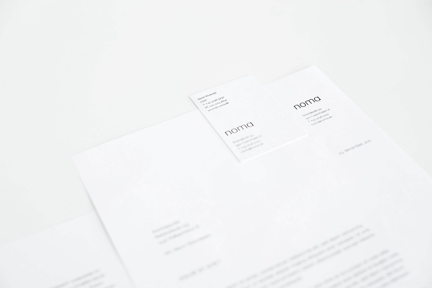 white letter and white business card with black bespoke 'noma' typeface