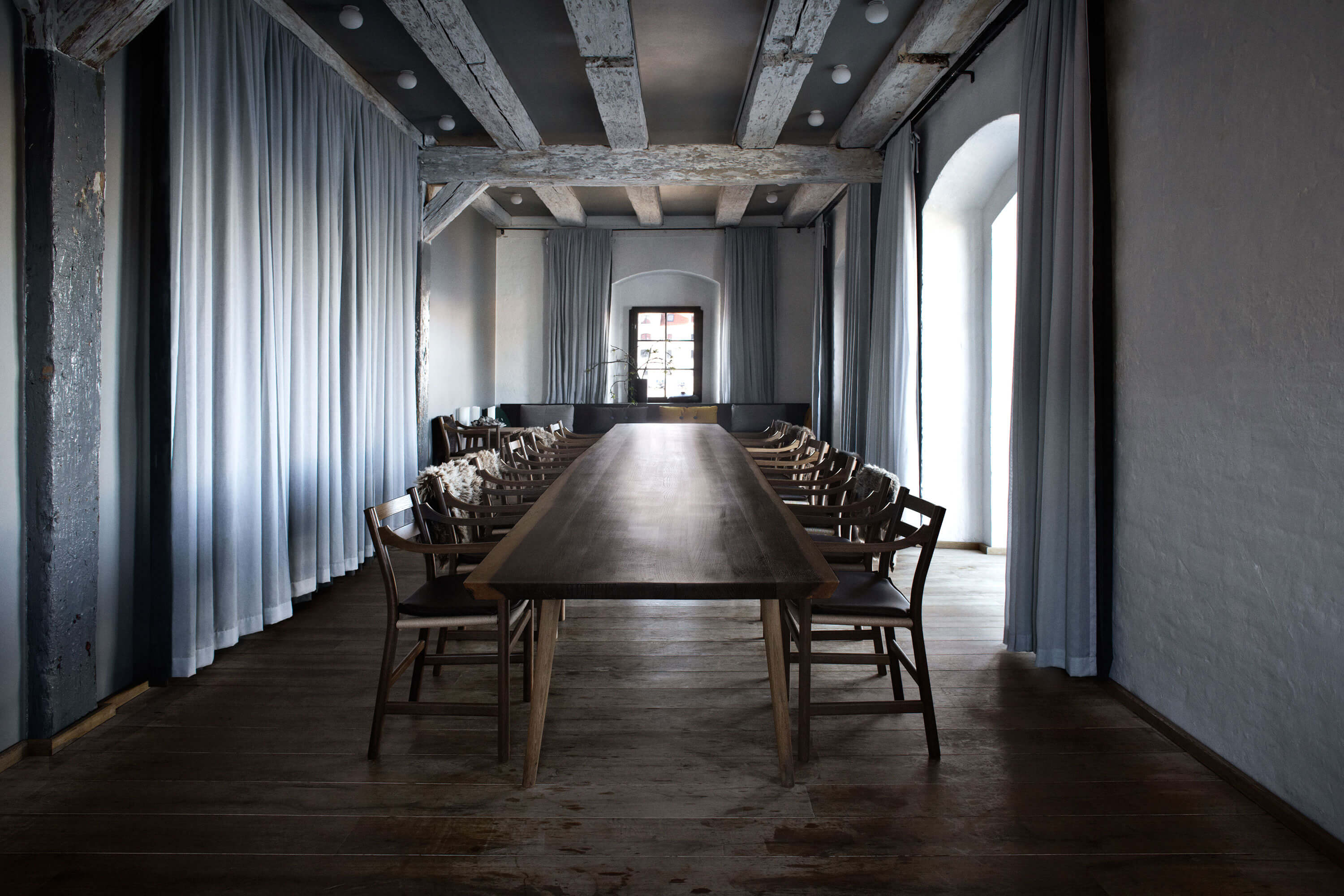 Colour photo of long wooden table with 14 wooden chairs in industrial room with curtains on one side and window on other side