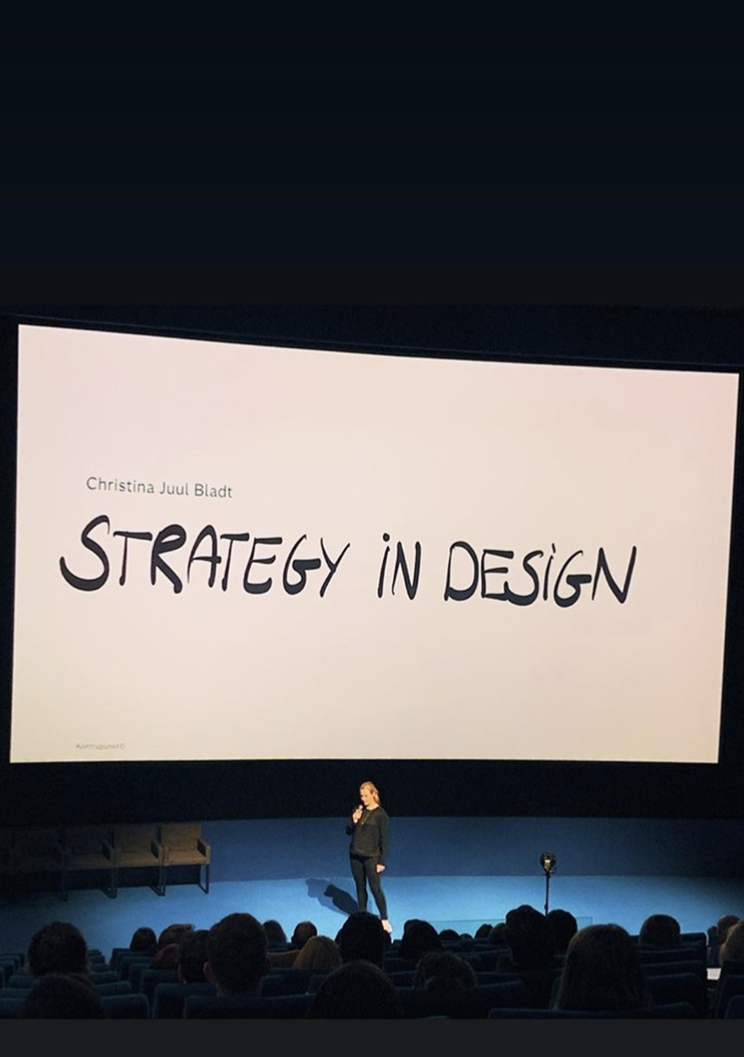 woman standing on conference stage with backdrop that says 'Strategy in Design'