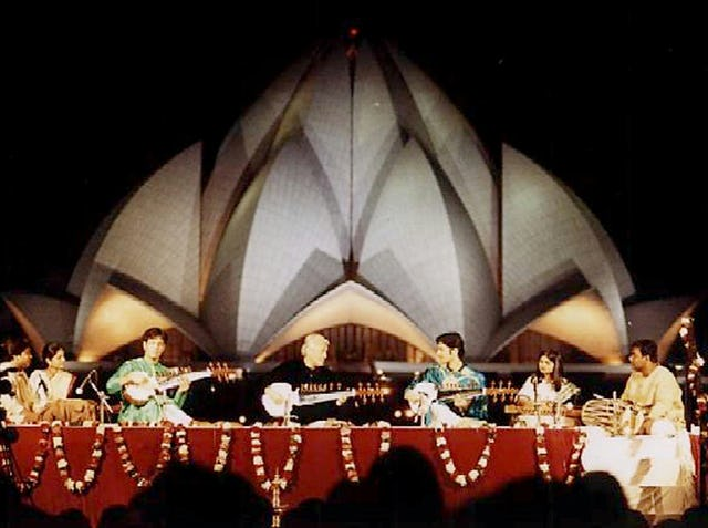 """The sarod maestro Amjad Ali Khan, assisted by his sons Amaan Ali Bangash and Ayaan Ali Bangash, performs in the shadow of the Baha'i House of Worship in New Delhi. The concert, entitled """"Sarod for Harmony,"""" was part of the opening program of the Colloquium on Science, Religion and Development."""
