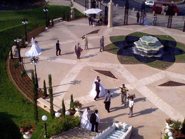 Three newlywed couples have their wedding photos taken on the entrance plaza of the Baha'i Terraces on Mount Carmel, a practice that has become very common among newlyweds in Haifa.