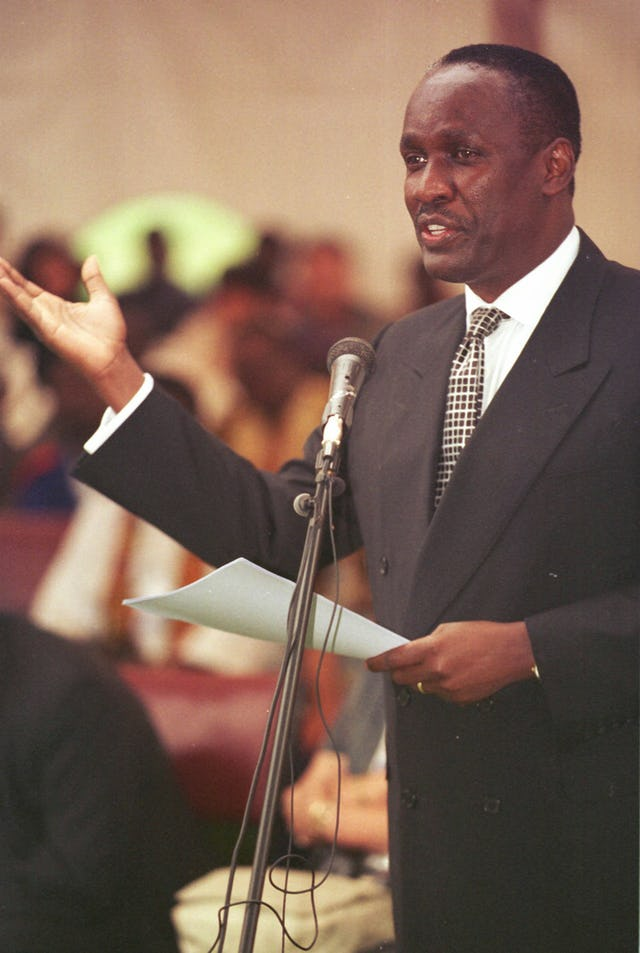 Captain Michael Mukula, Uganda's State Minister for Health, reads a statement from the President Yoweri Kaguta Museveni at a commemoration of the 50th anniversary of the Baha'i community of Uganda, held at the Baha'i House of Worship near Kampala on 2 August 2001. (Photo: Ryan Lash)