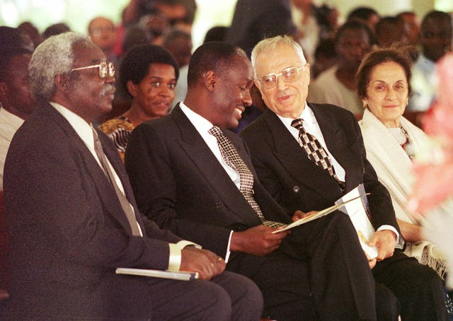 Mr. Ali Nakhjavani (third from left) speaks with Captain Michael Mukula, Uganda's State Minister for Health, at a commemoration of the 50th anniversary of the Baha'i community of Uganda held 2 August 2001 at the Baha'i House of Worship near Kampala. Mr. Nakhjavani, a member of the Universal House of Justice, was one of the six Baha'is who founded the Baha'i community in Uganda in 1951. (Photo: Ryan Lash)