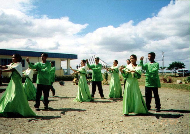 In a festive celebration, the Baha'i community of the Philippines officially inaugurated its new radio station on 26 November 2002. Shown here is a performance by the Tondod Public High School Dance Troupe.| The radio station building is in the background. It is the seventh Baha'i radio station in the world.