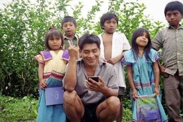 Victorino Rodriguez, with some of his students behind him, examines a Polaroid photograph of his primary school class in the tiny village of Quebrada Venado in the mountains of Western Panama.
