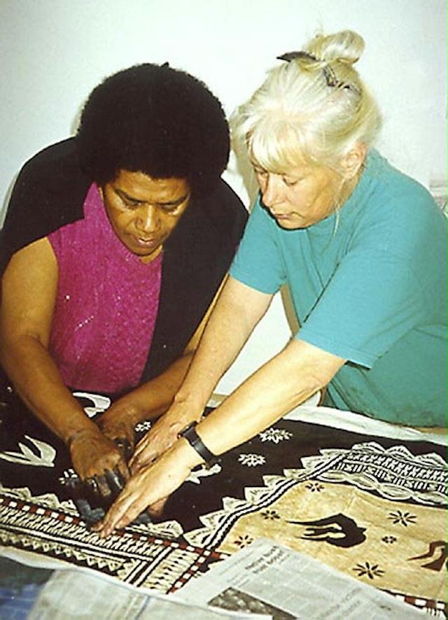 Leba Toki (left) and Robin White apply decorative elements to tapa cloth in Robin's studio in Masterton, New Zealand.