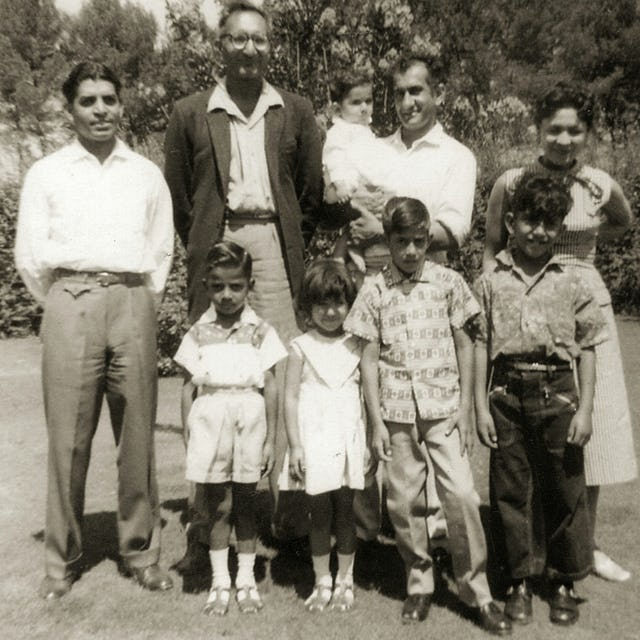 The first South African Indian to become a Baha'i was Dr. Abdul-Hak Bismillah (holding baby) in 1955. He is pictured with his wife, Joan. They are with Sombi Govind (left), Ismail Cassim and children.
