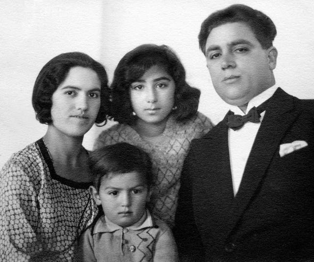 Gloria Faizi (center, rear) with her mother Najmieh (left), her father Rahmatu'llah Khan 'Ala'i (right), and her brother, Manuchihr.