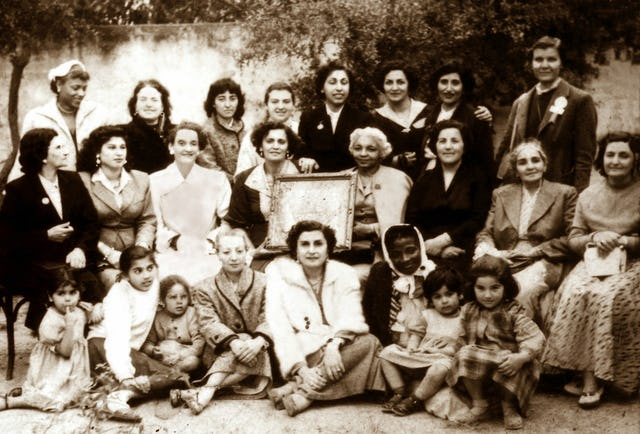 Elsie Austin (wearing coat and holding frame, seated center) with women attending the first Baha'i Convention in Tunis, Tunisia. 1956.