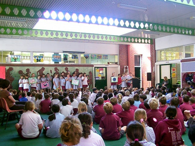 Members of a Baha'i Education in State Schools (BESS) class in Perth, Western Australia displaying their work at a school assembly.
