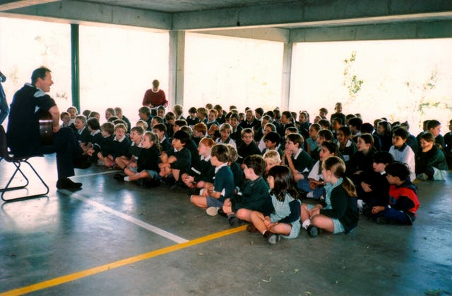 New Zealand musician Grant Hindin-Miller, a Baha'i, giving a concert for Baha'i Education in State Schools (BESS) students in the Rainworth State School in Brisbane, Queensland, Australia.