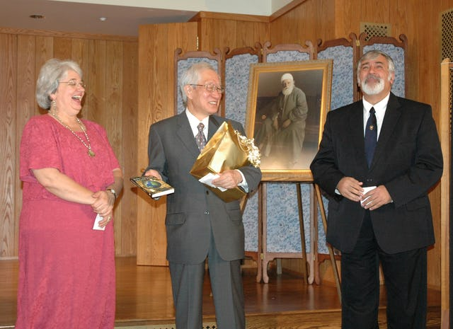 "Erica Toussaint, Japanese Ambassador Ryozo Kato, and Foad Katirai, after Dr. Katirai gave Ambassador Kato a copy of his book, ""Global Governance and the Lesser Peace,"" on 4 September 2005 at Green Acre Baha'i School."