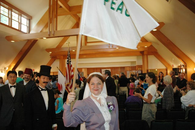 Anne Gordon Perry, portraying Green Acre Founder Sarah Farmer, holding a peace flag, during ceremonies on 4 September 2005 commemorating the 100th anniversary of the Portsmouth Peace Treaty.