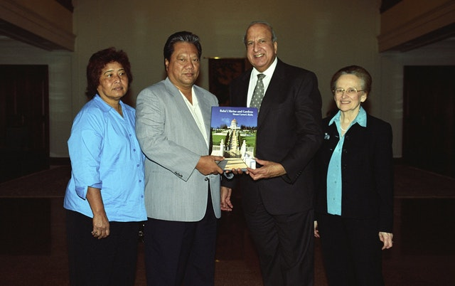 A member of the Universal House of Justice, Dr. Peter Khan, second from right, presenting President Kessai Note of the Marshall Islands with a book illustrating the Shrine of the Bab and its surrounding terraces. At left is Mrs. Mary Note and, at right, Dr. Janet Khan.