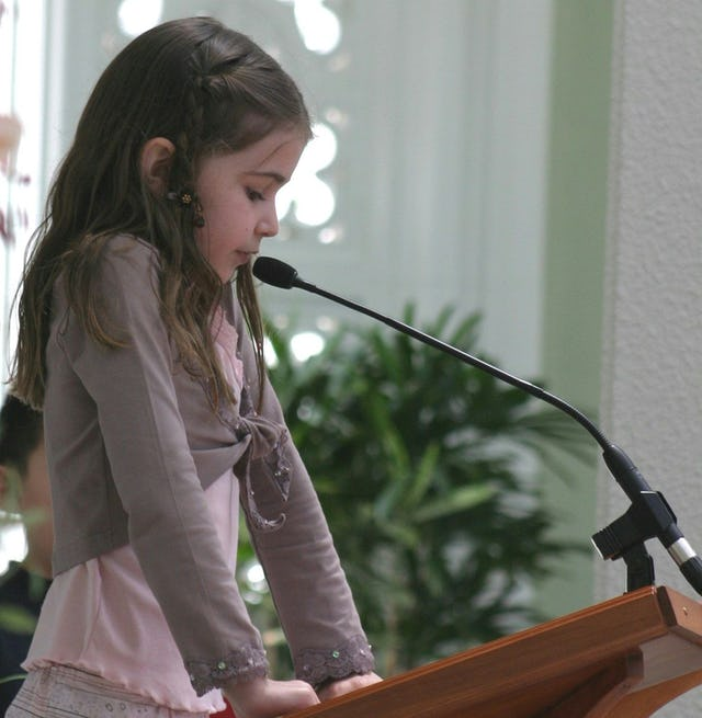 A pupil from a Sydney primary school, Chloe Maclean, reads a prayer at the service held in the House of Worship on Universal Children's Day. Photo by Saba Rouhani.