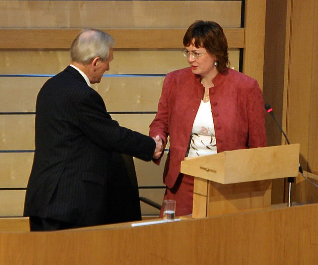 """The Presiding Officer of the Scottish Parliament, the Right Honorable George Reid MSP, left, congratulates Ms. Carrie Varjavandi of the Scottish Baha'i Community after she gave her """"Time for Reflection"""" address on 18 January 2006. (Photograph courtesy of and copyright by the Scottish Parliamentary Corporate Body 2005.)"""