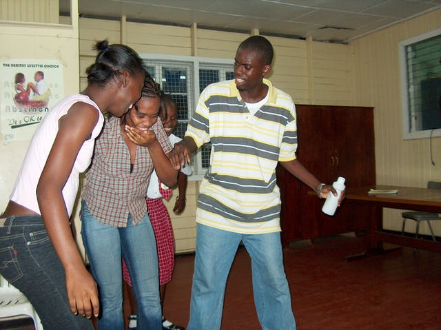 At the Future Club, Youth Can Move the World facilitators lead two dozen participants through a discussion on suicide prevention, which ended with the performance of various skits to illustrate what had been learned. At center is Rayana Jaundoo, pretending to drink Paraquat herbicide only to have her friends snatch the bottle away.