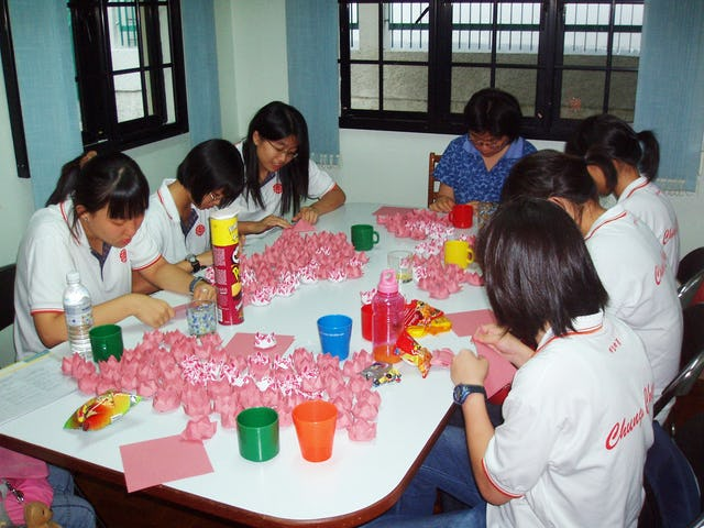 About 40 youth gathered at the Singapore Baha'i Center on 15 April 2006 to fold paper lotuses as part of the Project Million Lotus 2006. Shown here are six secondary school students from Chung Cheng High School with Baha'i Sabrina Han (center) in the blue shirt.