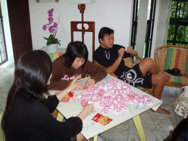 Project Million Lotus 2006 aims to have young people of all races and religions in Singapore make a million paper lotuses as symbols of purity and harmony. Shown, left to right, are Kuek Shao Zhen, Yuen Yi Ying, and Chong Ming Hwee, all Baha'is, folding paper flowers at the Singapore Baha'i Center on 15 April 2006.