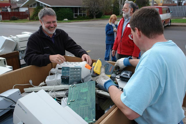 """Dr. Rodney Clarken, a Baha'i and one of the original signers of the Earth Keeper Covenant, at left, looks on as """"e-waste"""" is collected in a recycling bin in Marquette, Michigan. Also shown are Jean Soderberg (background, center) and Dennis McCowen (in red). All are Baha'is and all were participating in the Earth Keeper Clean Sweep on 22 April 2006. (Photo by Greg Peterson.)"""