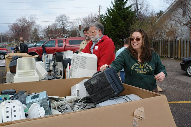 """Rehema Clarken, right, puts an old CD player into an """"e-waste"""" recycling bin during the Earth Keepers Clean Sweep in Marquette, Michigan, on 22 April 2006. In the red jacket is Dennis McCowen. Both are Baha'is. (Photo by Greg Peterson.)"""