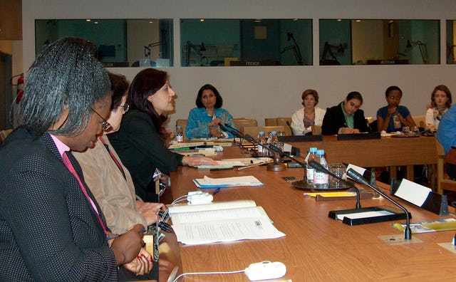 """Beyond Violence Prevention: Creating a Culture to Enable Women's Security and Development,"" a panel discussion at the United Nations on 8 September 2006, was hosted by the Baha'i International Community and the International Presentation Association. It was held as part of the 59th Annual United Nations Department of Public Information/Non-Governmental Organization conference. Closest to the camera is Letty Chiwara, a program specialist with the Africa section of the United Nations Fund for Women (UNIFEM). To her left is Joan Burke. Fulya Vekiloglu of the Community, leaning forward, was the panel's moderator."