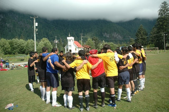 Both teams in prayer before the beginning of the game.