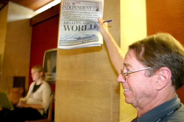 Arthur Dahl, president of the International Environment Forum, displays the front page of The Independent, published on 16 September 2006, with a major story about climate change. (Photograph by Gemma Parsons)