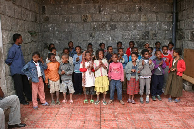 The children practice a song they plan to perform for their parents.
