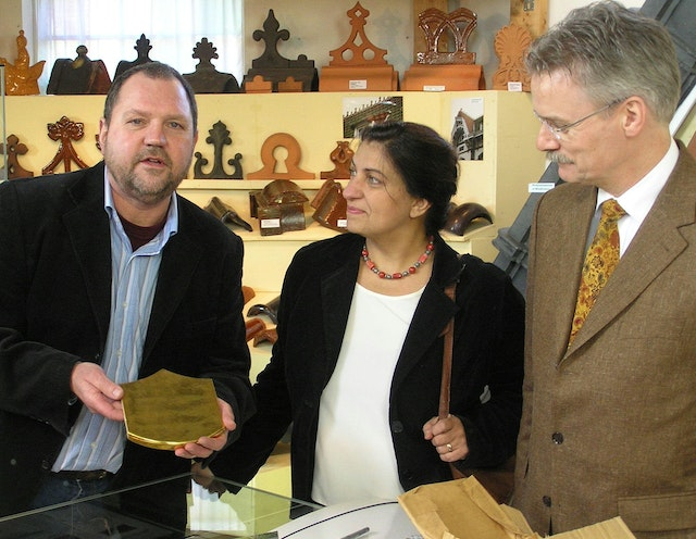 Huub Mombers, left, receives a gilded tile from the Shrine of the Bab for his museum in Alem, in Holland. Offering the tile on permanent loan, on behalf of the Baha'is of the Netherlands, are Elaheh Verhey-Shahgholi, center, and Jelle de Vries. The ceremony was on 3 February 2007.