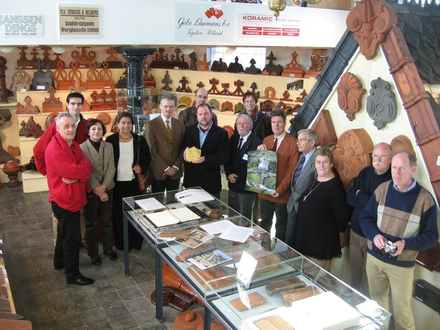 The Dutch Roof Tile Museum is located in an old church and contains several thousand roof tiles. Shown here are owner Huub Mombers, in center holding the gilded tile, and others present for the ceremony last month.