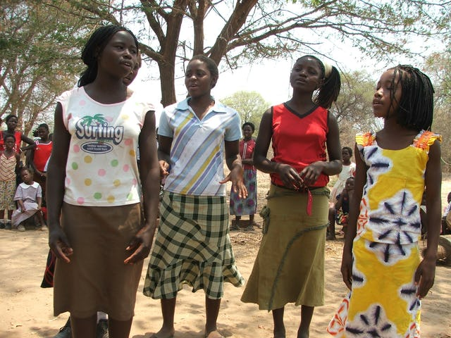 """Young teens join to recite a poem at the launch on 6 October of 38 new """"junior youth"""" groups in Sinazongwe District in southern Zambia."""