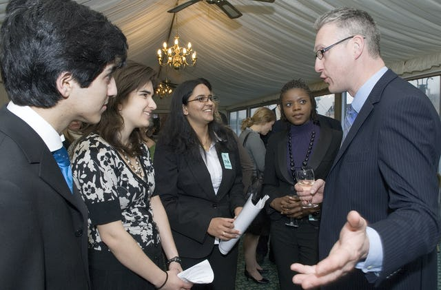 Member of Parliament Lembit Opik talks with four young speakers at the reception of the All Party Parliamentary Friends of the Baha'is group on 22 April 2008. From left are Collis Tahzib, Jenna Nicholas, Lavina Hassasing and Ruth Banda. Photograph: Andisheh Eslamboli.