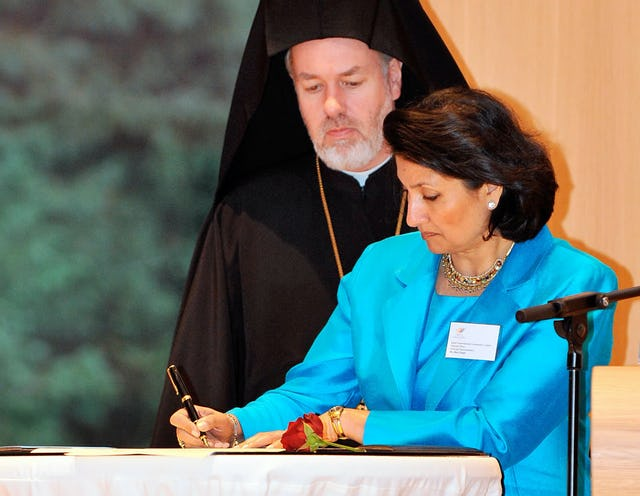 Baha'i representative Bani Dugal signs the 2008 Faith in Human Rights statement on 10 December at The Hague. Looking on is the Right Reverend Bishop Athenagoras (Peckstadt) of Sinope, of Belgium.