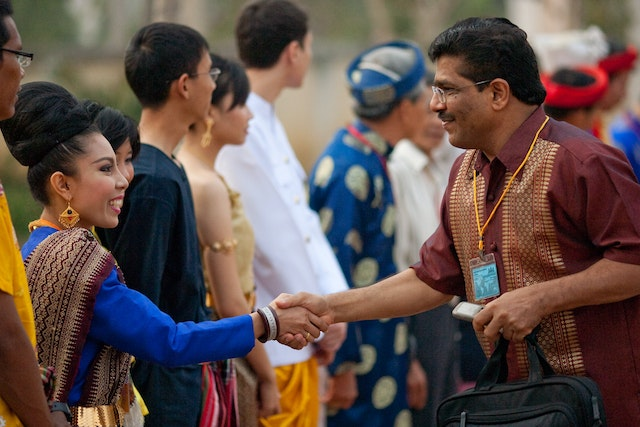 Greeters in traditional costumes from the participating countries of Cambodia, Laos, Thailand, and Vietnam welcome people arriving to the Baha'i conference in Battambang.