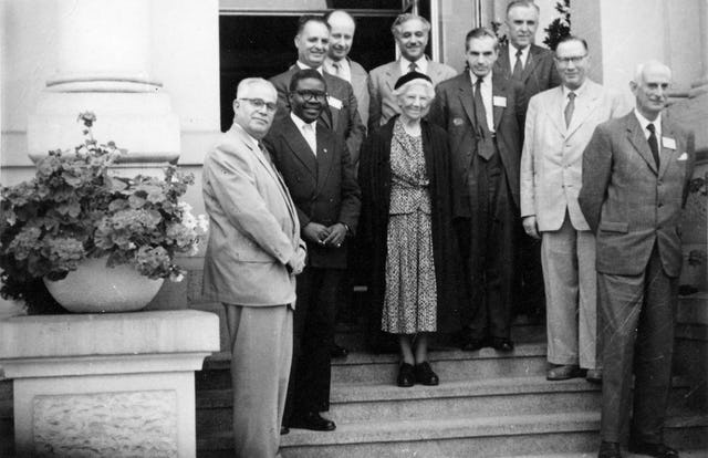 Amelia Collins, center, was the representative of the Guardian of the Baha'i Faith at the July 1958 gathering in Frankfurt. Other Hands of the Cause present, from left, were Jalal Khazeh, Enoch Olinga, Zikrullah Khadem, Adelbert Muhlschlegel, Hasan Balyuzi, John Ferraby, John Robarts, Hermann Grossmann, and Ugo Giachery. Also present but not pictured was Musa Banani. (Baha'i World Centre photograph)