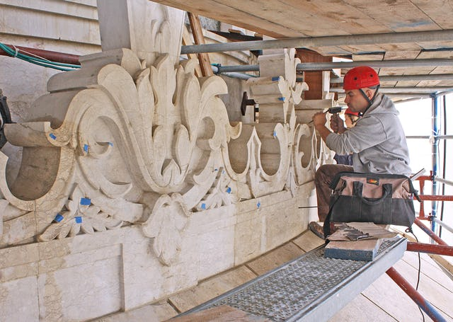 Workers are going over the entire stone exterior of the shrine and repairing every spot that shows signs of damage from 50 years of exposure to the elements. Jubin Nakhai, shown here, is an experienced stone carver from Canada. (Baha'i World Centre photo. All rights reserved.)