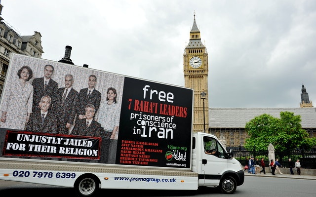 """One of United4Iran's mobile billboards has been launched in London, England. It features the image of the seven Baha'i leaders and the slogan, """"Unjustly jailed for their religion""""."""