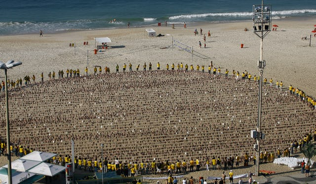 In Brazil, human rights campaigners circle around almost 8,000 images depicting the faces of Iran's seven imprisoned Baha'i leaders, on Rio's Copacabana Beach. The photographs were arranged to represent the world, and the union of people of all races and nations.